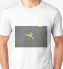 A green pond frog in black water. T-Shirt