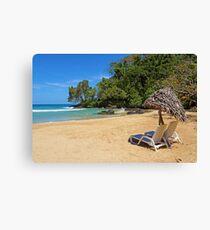 Lounge chairs with parasol on tropical beach Canvas Print