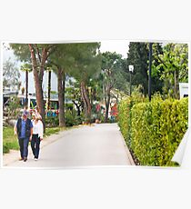 a couple walking alone the side of lake garda Poster