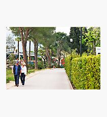 a couple walking alone the side of lake garda Photographic Print