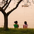 two people sitting on the bank side by xxnatbxx