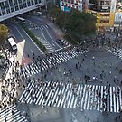 Elevated view of a crowed of pedestrians crossing a four way zebra crossing at Shibuya crossing in central Tokyo, Japan by PhotoStock-Isra
