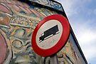 Road sign juxtaposed against street art by David Carton