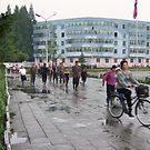 After the rain: mum, baby, bike by Marjolein Katsma