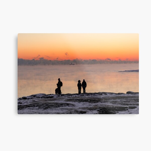 Silhouettes of people standing on shore fo the foggy sea at sunset time in Helsinki Metal Print
