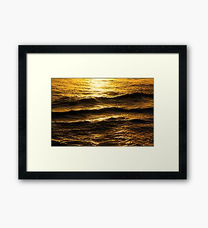Golden glow on water and waves Framed Print