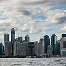 A small airplane flies above the skyscrapers of Old Toronto by Sergey Orlov