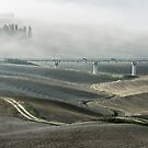 An old ground and a modern linear roads run through misty Tuscany fields by Sergey Orlov