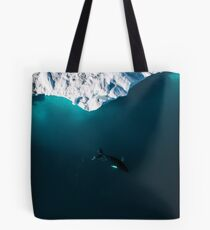 Aerial of a lone Humpback whale in front of an iceberg in Greenland Tote Bag
