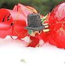 Miniature snowman  with transparent red Christmas ball in snow by pogomcl