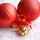 Two red Christmas balls with a brass jingle bell on whtie damask satin by pogomcl