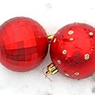 Two red satin glass Christmas balls on snow by pogomcl