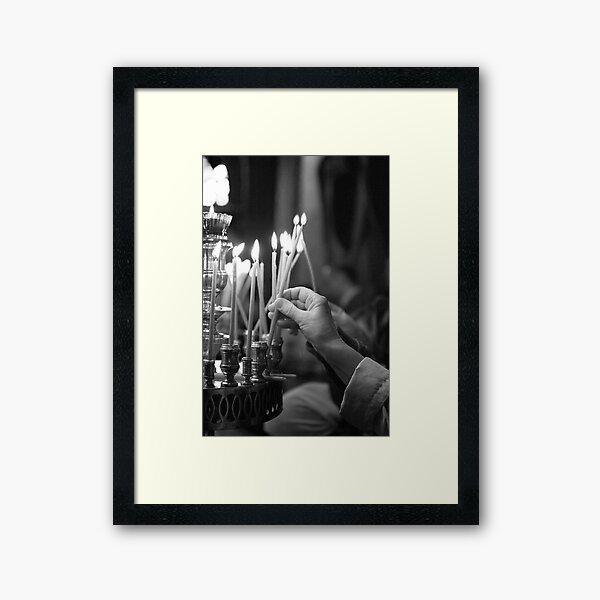 Lighting a candle Framed Art Print