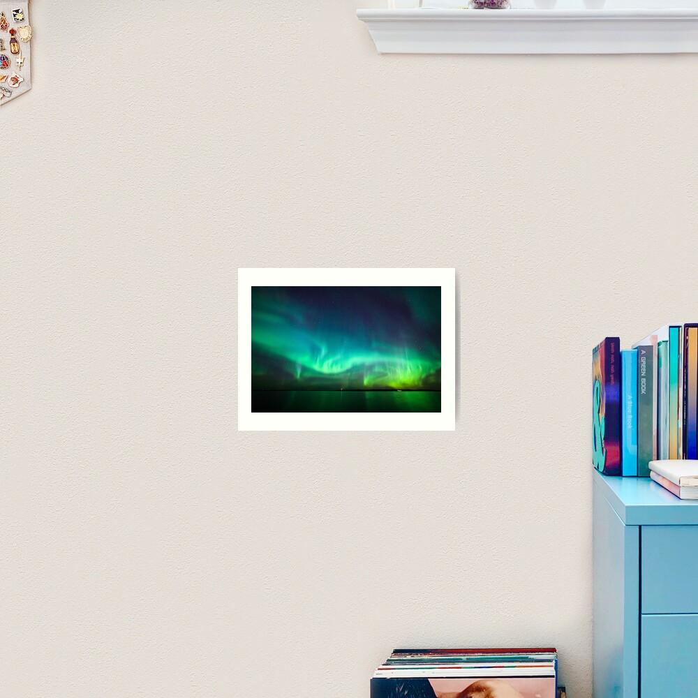 Northern lights glow over lake Art Print