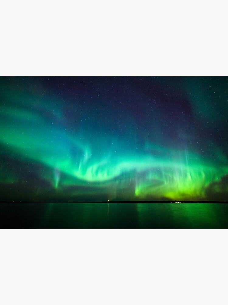 Northern lights glow over lake by Juhku