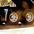 Trucks - Rear Wheels & Axel Detail of a Dump Truck with Dust Flying by Buckwhite