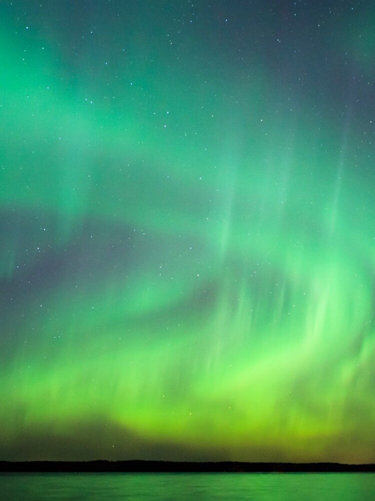 Northern lights over lake in Finland by Juhku