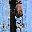 Hand knocker on blue door by Sue Frank
