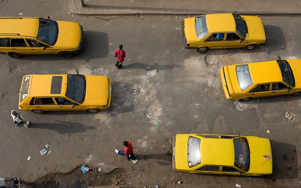 Taxis on Broad Street in Monrovia, Liberia by Christopher Herwig