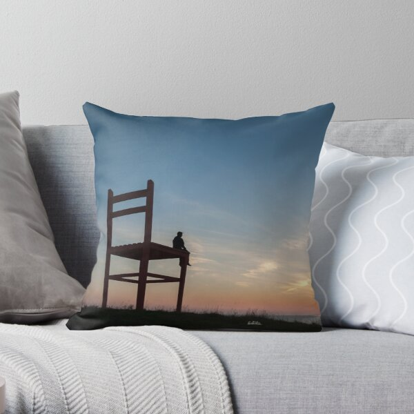 photograph a man on a huge chair at sunset in Îles-de-la-Madeleine Throw Pillow