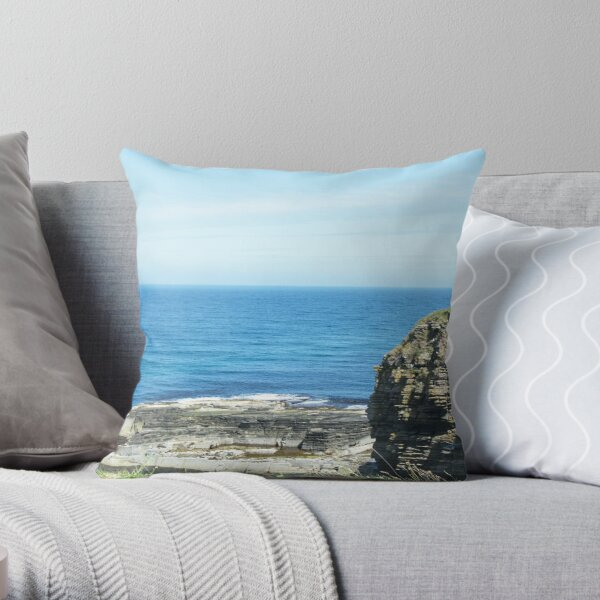 Rocks and raised ledge in sea Throw Pillow