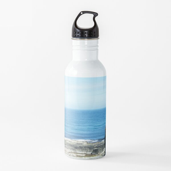 Rocks and raised ledge in sea Water Bottle