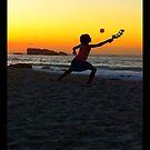 Girl playing beach ball. by Tom Mostert