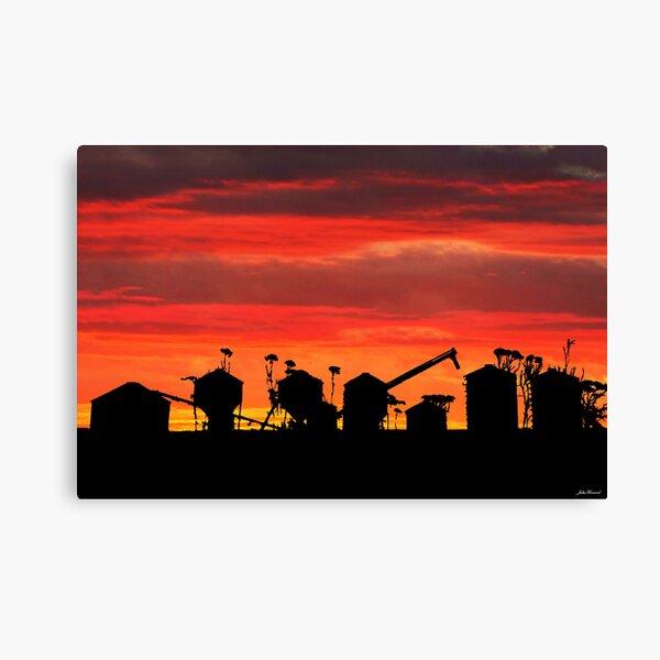 Sunset over wheat silos Canvas Print
