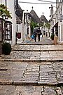 Shopping in the Rain - Alberobello Italy by Debbie Pinard